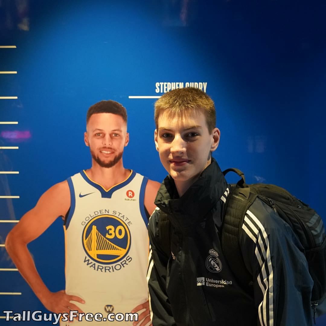 Olivier Rioux bending down next to 6ft3 NBA player Stephen Curry